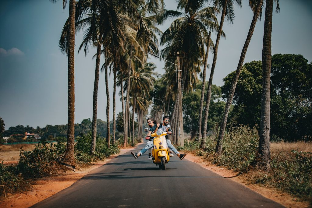 Men riding a Vespa on a palm lined road
